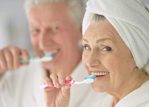 Importancia de la higiene dental en las personas mayores: Una mujer anciana se cepilla los dientes